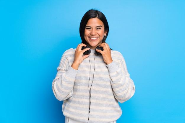 ヘッドフォンでセーターを持つコロンビア少女 Premium写真