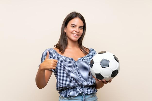 サッカーボールを保持している孤立した壁の上の少女 Premium写真