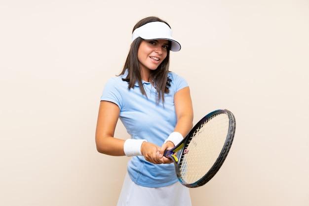 孤立した壁の上のテニスの若い女性 Premium写真