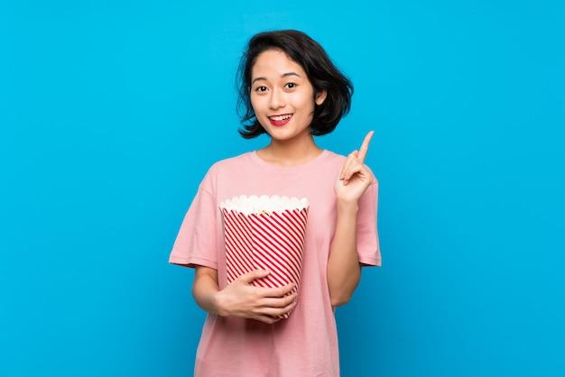 素晴らしいアイデアを指しているポップコーンを食べるアジアの若い女性 Premium写真
