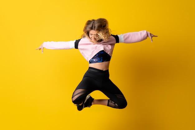 孤立した黄色の上で踊り、ジャンプ都市バレリーナ Premium写真
