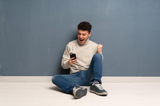 勝利の位置に電話で床に座っている若い男 Premium写真