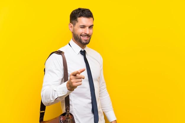 あなたに孤立した黄色のポイント指でハンサムな実業家 Premium写真