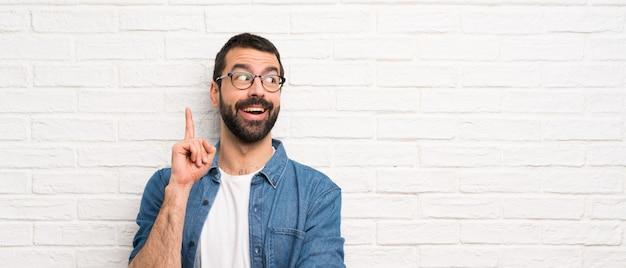 指を上向きのアイデアを考えて白いレンガの壁の上のひげを持つハンサムな男 Premium写真