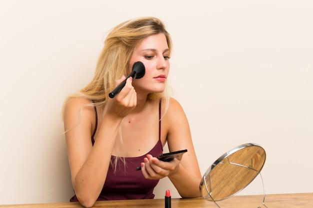 テーブルの化粧品で若いブロンドの女性 Premium写真