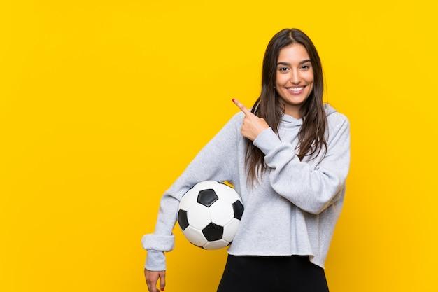 製品を提示する側を指している孤立した黄色の壁の上の若いフットボール選手女性 Premium写真