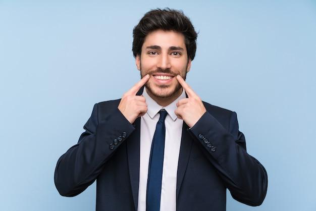 幸せで快適な表情に笑みを浮かべて分離の青い壁の上のビジネスマン Premium写真