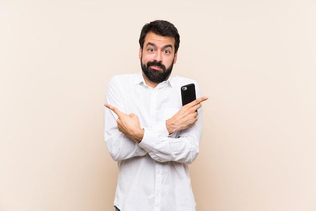 疑いのある側面を指している携帯電話を保持しているひげを持つ若者 Premium写真