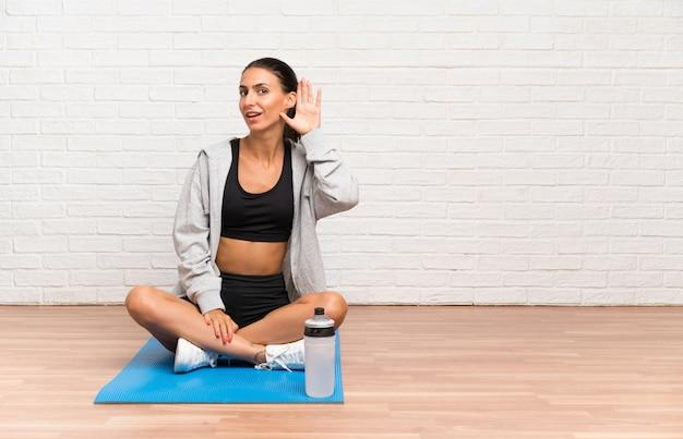 何かを聞いてマットで床に座っている若いスポーツ女性 Premium写真