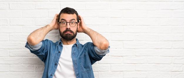 白いレンガの壁の上のひげを持つハンサムな男はイライラし、頭に手を取ります Premium写真