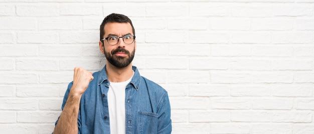 Красивый мужчина с бородой над белой кирпичной стеной Premium Фотографии