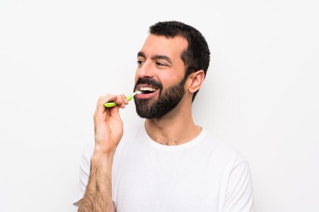 孤立した白い壁に歯を磨くひげを持つ男 Premium写真