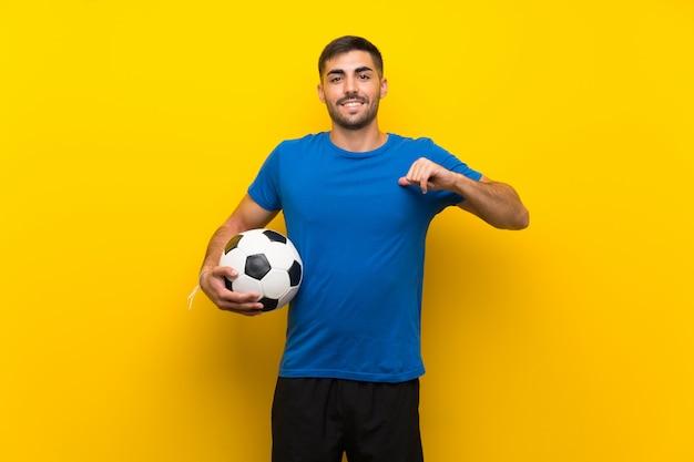Молодой красивый футболист человек над изолированной желтой стеной гордый и самодовольный Premium Фотографии