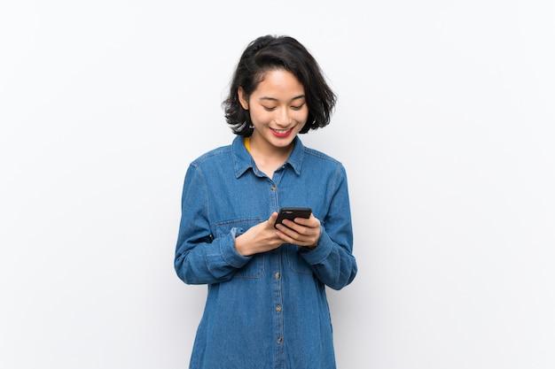 携帯電話でメッセージを送信する孤立した白い壁の上のアジアの若い女性 Premium写真