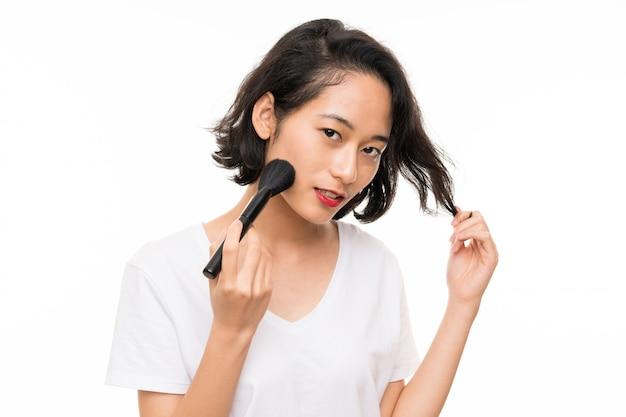 化粧ブラシで孤立した壁の上のアジアの若い女性 Premium写真