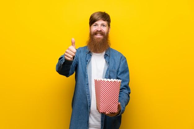ポップコーンのボウルを保持している孤立した黄色の壁の上の長いひげを持つ赤毛の男 Premium写真
