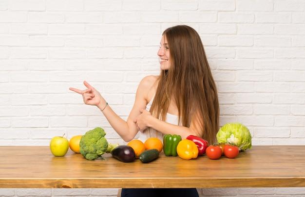 側に指を指している多くの野菜を持つ若い女性 Premium写真