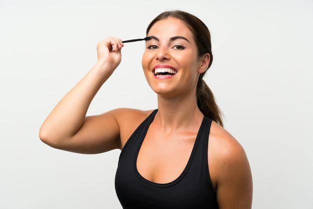 化粧品のラッシュとマスカラーを適用する分離の白い壁の上の若い女性 Premium写真
