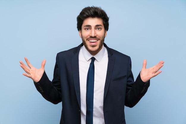 Бизнесмен над изолированной синей стеной с шокирован выражением лица Premium Фотографии