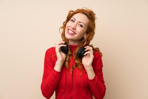 ヘッドフォンで音楽を聴くタートルネックのセーターと赤毛の女性 Premium写真