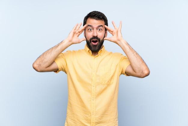 Молодой человек с бородой над синей стеной с выражением удивления Premium Фотографии