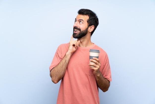 見上げながらアイデアを考えて分離の青い壁にコーヒーを持ち帰るひげを持つ若者 Premium写真