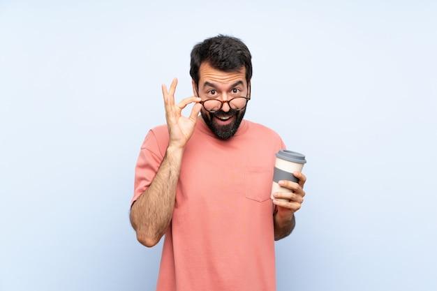 ひげを持った若い男がメガネで分離された青い壁にコーヒーを奪うと驚いた Premium写真