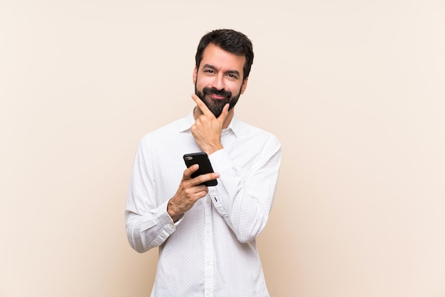 モバイル思考を保持しているひげと若い男 Premium写真