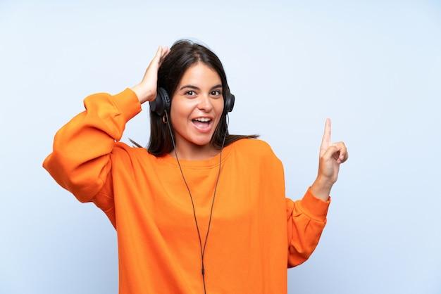 驚いたと側に指を指している分離の青い壁の上の携帯電話で音楽を聴く若い女性 Premium写真