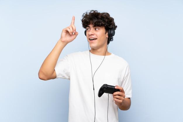 指を持ち上げながら解決策を実現しようとしている分離の青い壁を越えてビデオゲームコントローラーで遊ぶ若い男 Premium写真