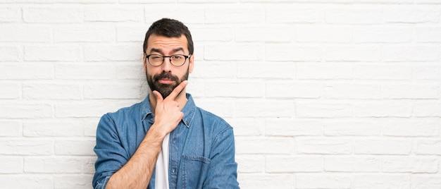 白いレンガ壁思考上のひげを持つハンサムな男 Premium写真
