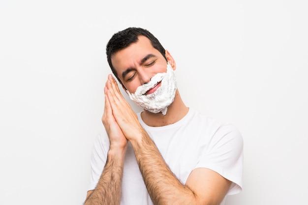 愛らしい表情で睡眠ジェスチャーを作る分離の白い壁に彼のひげを剃る男 Premium写真