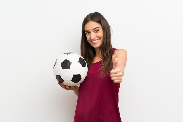 サッカーボールを保持している孤立した白い壁の上の若い女性 Premium写真