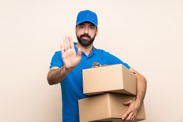 Доставка человек с бородой на изолированной стене, делая остановки жест Premium Фотографии
