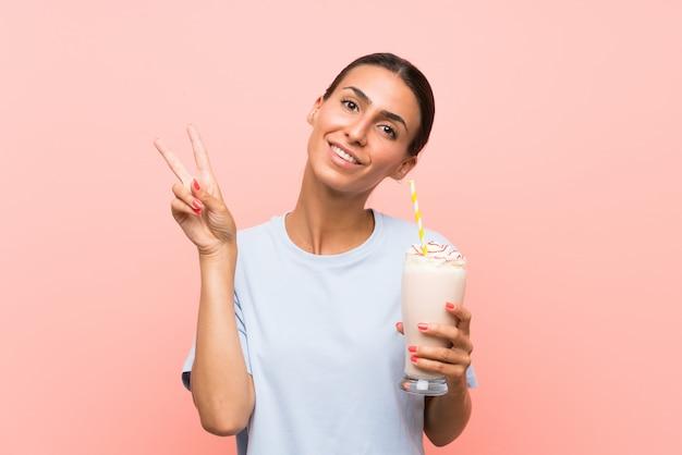 笑みを浮かべて、勝利のサインを示す分離のピンクの壁にいちごのミルクセーキを持つ若い女性 Premium写真
