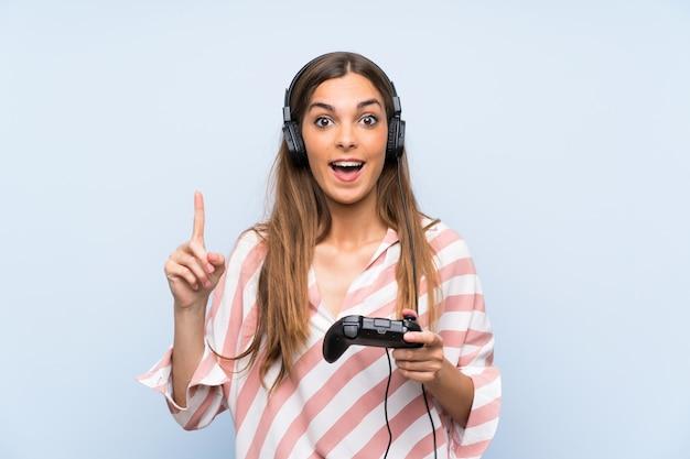 素晴らしいアイデアを指している分離の青い壁の上のビデオゲームコントローラーで遊ぶ若い女性 Premium写真