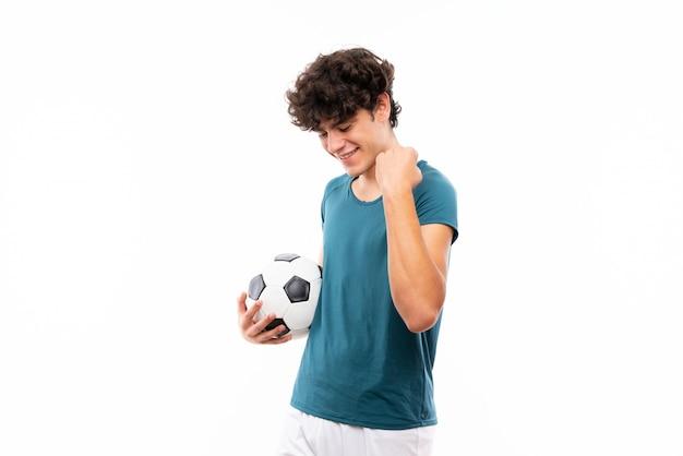 勝利を祝う孤立した白い壁の上の若いフットボール選手男 Premium写真