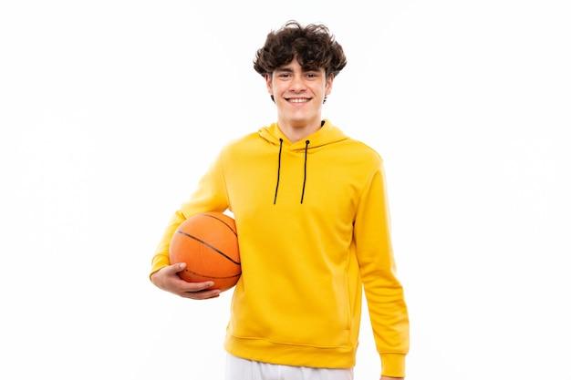 多くの笑みを浮かべて分離の白い壁の上の若いバスケットボールプレーヤー男 Premium写真