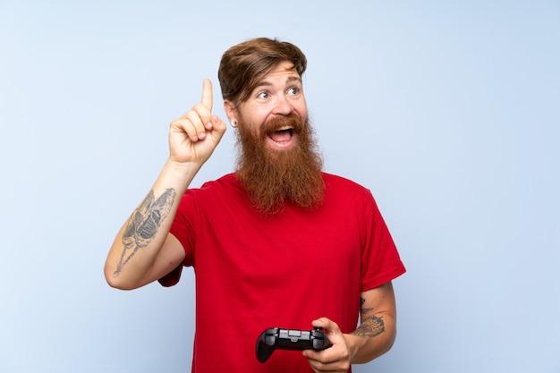 指を持ち上げながら解決策を実現しようとしているビデオゲームコントローラーで遊んで長いひげを持つ赤毛の男 Premium写真