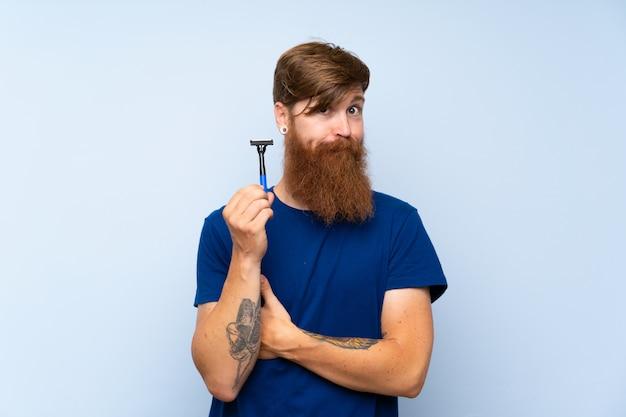 Рыжий мужчина бреет бороду над изолированной синей стеной, делая сомнение жест, поднимая плечи Premium Фотографии