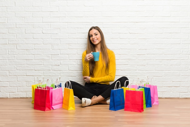 熱い一杯のコーヒーを保持している買い物袋の多くを持つ若い女の子 Premium写真