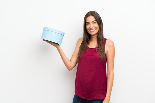 ギフト用の箱を保持している孤立した白い壁の上の若い女性 Premium写真