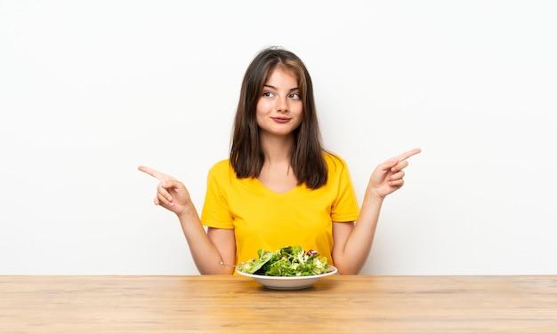 疑問を持つラテラルを指しているサラダと白人の女の子 Premium写真