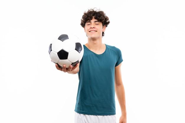 孤立した白い壁の上の若いフットボール選手男 Premium写真