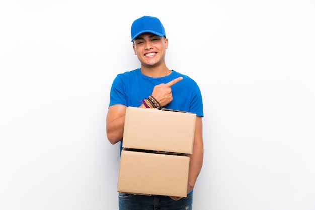 Доставка человек над белой стене, указывая на сторону, чтобы представить продукт Premium Фотографии