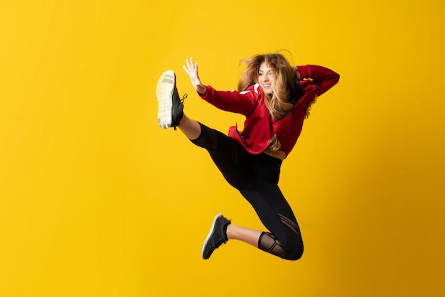 孤立した黄色の壁の上に踊り、ジャンプ都市バレリーナ Premium写真