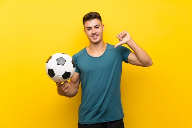 孤立した黄色の壁を越えて誇りと自己満足のハンサムな若いフットボール選手男 Premium写真