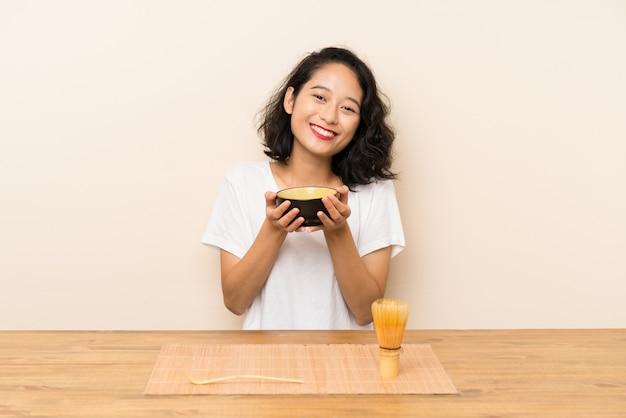 お茶抹茶を持つ若いアジアの女の子 Premium写真