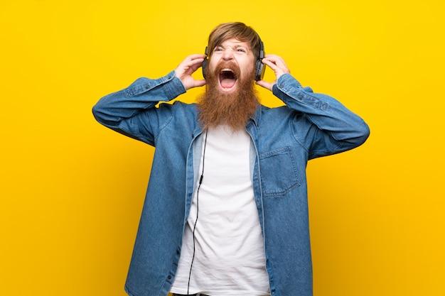 ヘッドフォンで音楽を聞いて孤立した黄色の壁に長いひげを持つ赤毛の男 Premium写真
