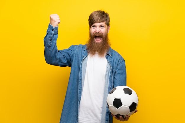 サッカーボールを保持している孤立した黄色の壁の上の長いひげを持つ赤毛の男 Premium写真